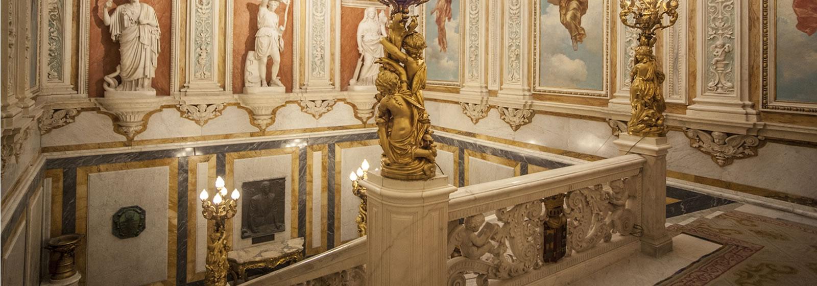 Vistas del interior del Palacio de Santoña, parte superior de la escalera principal, donde se aprecian altos techos y esculturas y murales.